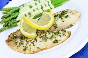 Fresh baked Tilapia fish dinner with asparagus and Hollandaise s