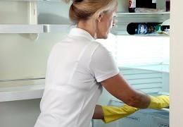 Seniorin putzt Kühlschrank